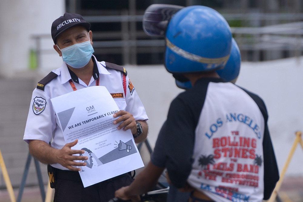 A security guard explains to customers as malls are closed from May 9-11 as part of HIDE requirement during MCO 3.0 at GM Klang Wholesale City May 9, 2021. — Picture by Miera Zulyana