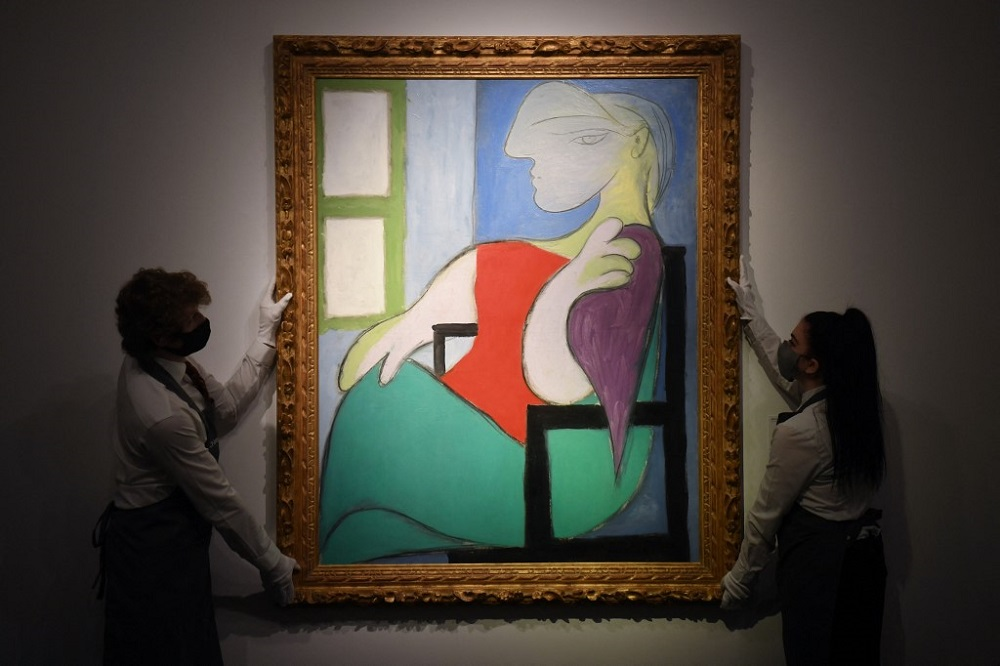Gallery workers display an artwork titled 'Woman sitting by a window (Marie-Therese)' at Christie's in New York April 22, 2021. — AFP pic