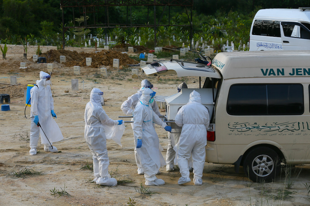 Covid 19 victims body arrive for funeral service handled by workers equipped with personal protective suit at Kampung Sungai Pusu Muslim cemetery May 22,2021.— Picture by Ahmad Zamzahuri