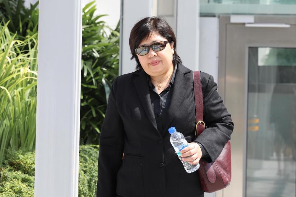 潘秋玉周一离开新加坡国家法院大楼时,被媒体拍到仍不愿意戴口罩。-TODAY-