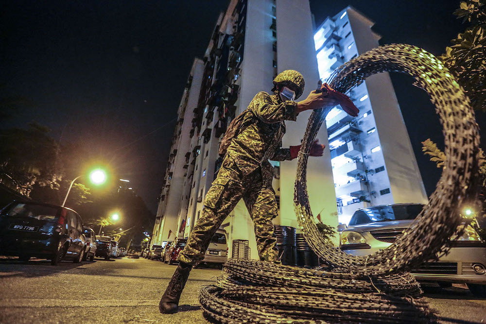 Members of the Malaysian Armed Forces (ATM) are seen installing barbed wire around at Kampung Limau People's Housing Project (PPR) area in Kuala Lumpur following the enhanced movement control order (EMCO) from May 23 to June 5. — Picture by Hari Anggara