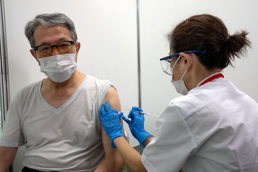 A pensioner receives the Moderna vaccine at the newly-opened mass vaccination centre in Tokyo, Japan May 24, 2021. — Carl Court/Pool via Reuters