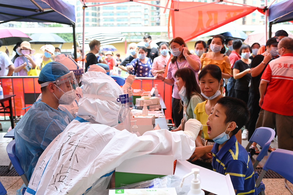 A medical worker collects a swab from a resident during a mass testing for Covid-19 at a makeshift testing site at a stadium in Guangzhou, China May 30, 2021. — cnsphoto via Reuters