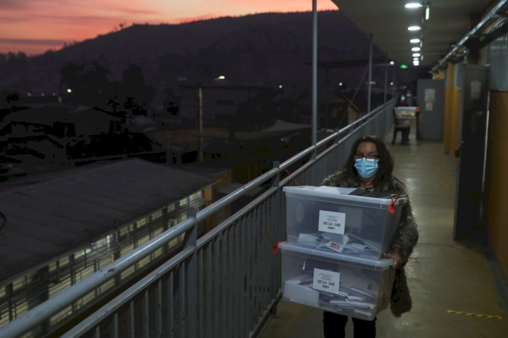 A poll worker carries boxes containing votes for storage at the end of a polling day during the elections for governors, mayors, councillors and constitutional assembly members to draft a new constitution to replace Chile's charter, in Santiago, Chile M