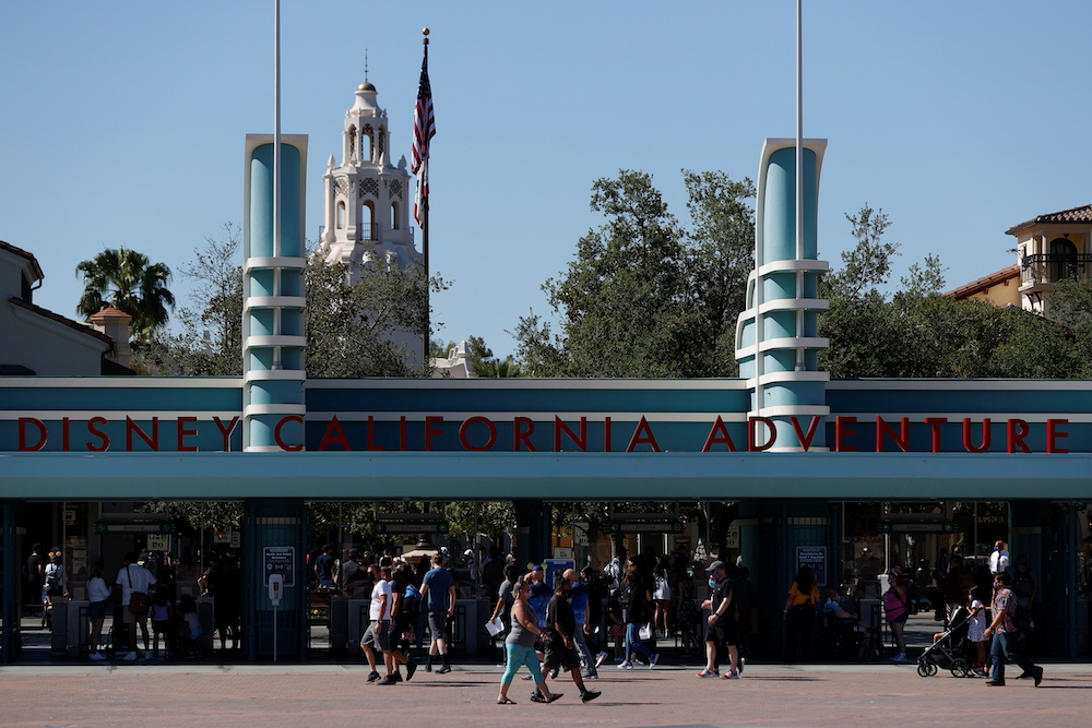 People walk outside Disneyland Park on its reopening day amidst the coronavirus disease outbreak, in Anaheim, California, US, April 30, 2021. — Reuters pic