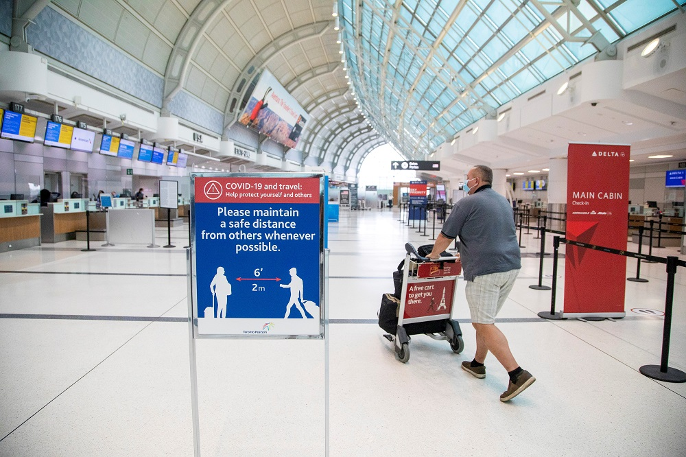 A man pushes a baggage cart wearing a mandatory face mask as a 'Healthy Airport' initiative is launched for travel, to slow the spread of Covid-19 at Toronto Pearson International Airport in Toronto, Ontario, Canada June 23, 2020. ― Reuters file pic