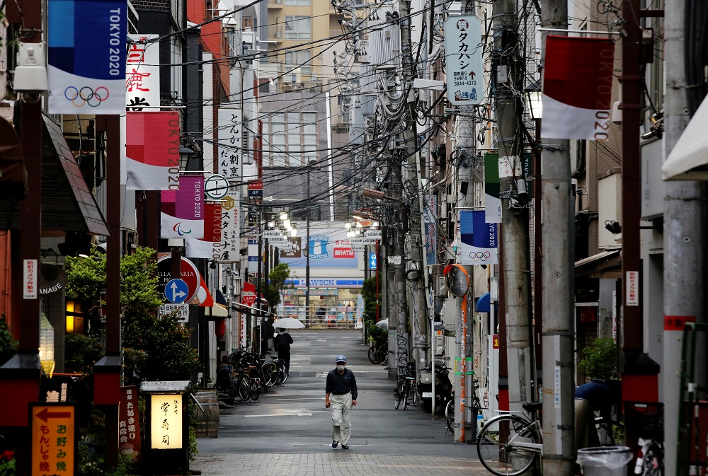 A man wearing a protective face mask walks in a local shopping street decorated with Tokyo 2020 Olympic Games flags, in Tokyo, Japan May 7, 2021. ― Reuters pic