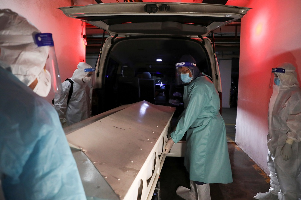 Malaysian Muslim cleric Rafie Zainal and his team members move a body of a Covid-19 victim to a van before burial at a hospital mortuary, in Kuala Lumpur May 23, 2021. ― Reuters pic