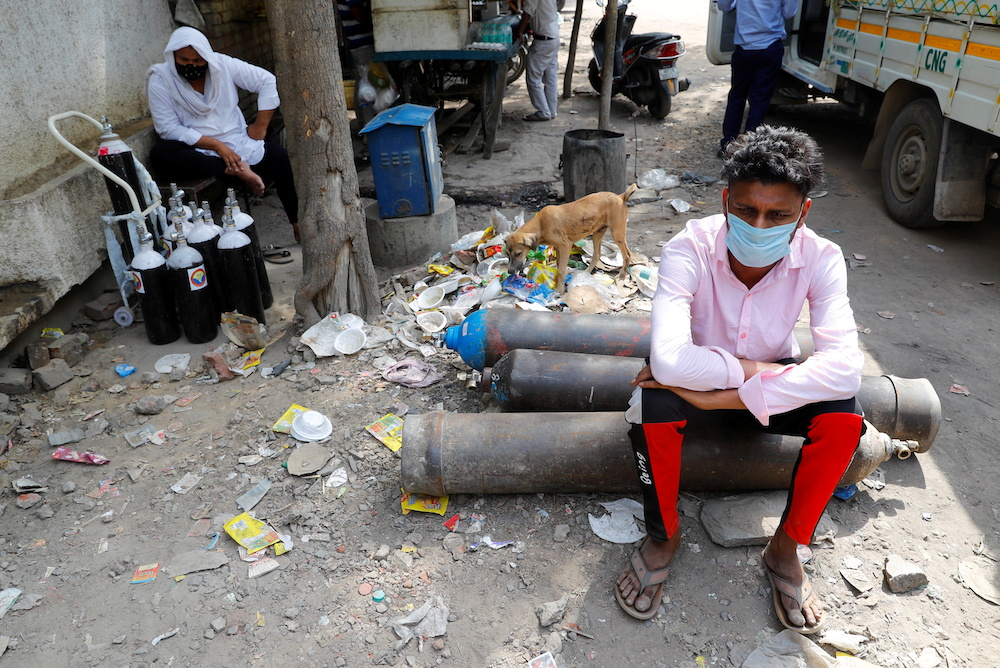 Sumit Kumar, 28, sits on an oxygen cylinder as he waits outside a factory to get it refilled, amidst the spread of the coronavirus disease in New Delhi, India, April 28, 2021. — Reuters pic