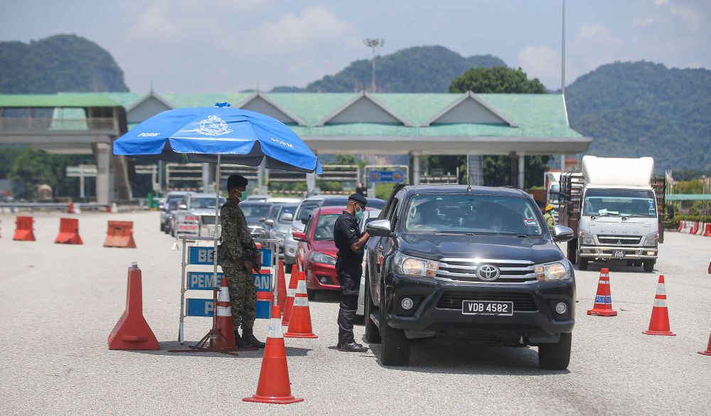 Police personnel conduct checks on vehicles at a roadblock during MCO 3.0 at the Ipoh Selatan Toll May 10, 2021. — Picture by Farhan Najib