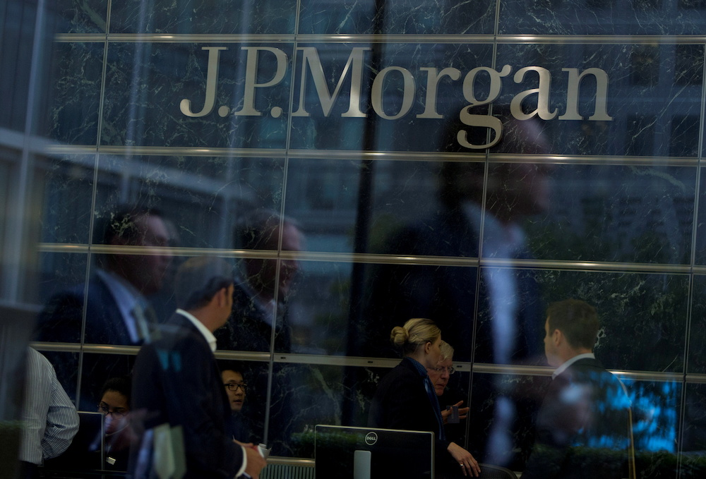 Workers are reflected in the windows of the Canary Wharf offices of JP Morgan in London September 19, 2013. ― AFP