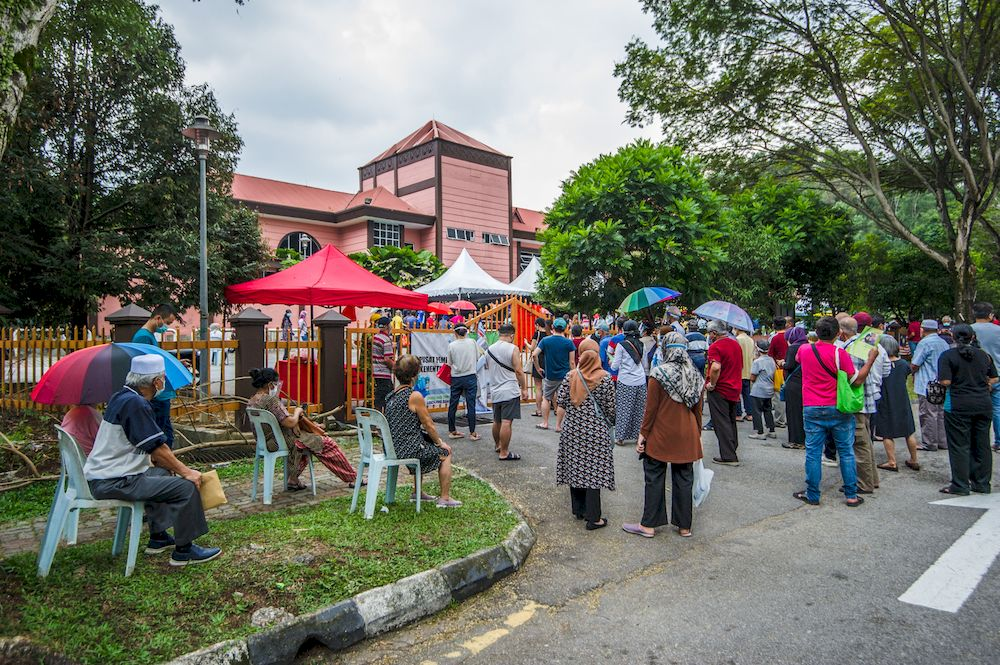 Picture shows a day before the implementation of MCO 3.0, people queuing up to receive the Covid-19 vaccine as part of a mass vaccination program, at Bandar Manjalar community hall vaccination centre in Kuala Lumpur, May 24, 2021. — Picture by Shafwan Zaidon