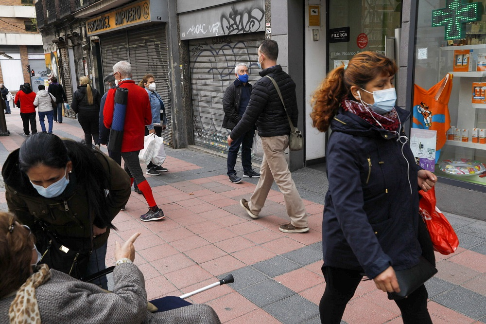 People stand next to closed-down businesses as they wait to enter a pharmacy, amid the Covid-19 pandemic, in Madrid March 12, 2021. ― Reuters file pic