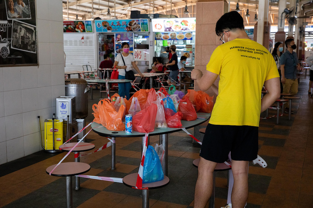A WhyQ hawker food delivery staff sorting out takeaway orders at Ghim Moh Hawker Centre on May 28, 2021. The older generation of hawkers must grapple with the changing habits of their customers, especially the younger ones, who are now getting used to hav