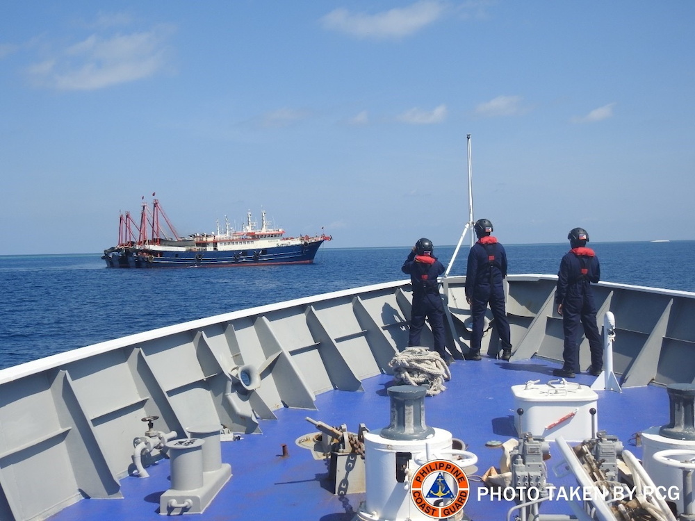File photo of Philippine Coast Guard personnel surveying several ships believed to be Chinese militia vessels in Sabina Shoal in the South China Sea, in a handout photo distributed by the Philippine Coast Guard on May 5 and taken according to source on April 27, 2021. —