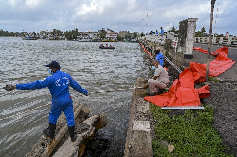 Sri Lankan Coast Guard personnel lay booms at an estuary in Negombo, north of Sri Lankan capital Colombo on May 28, 2021. — AFP pic