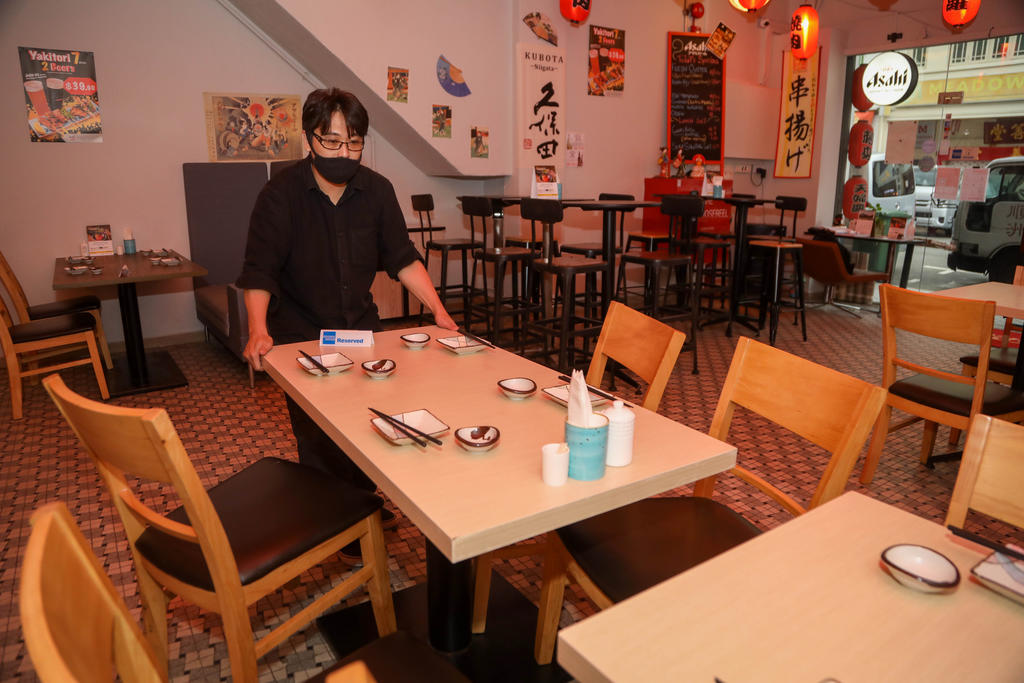 A worker at Hinode Izakaya and Bar separating tables that would normally seat up to eight. ― TODAY pic