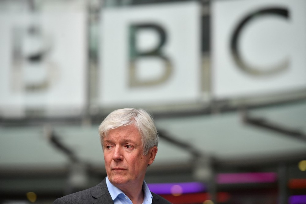 In this file photo taken on November 15, 2018 the Director-General of the BBC Tony Hall is seen waiting to greet Britain's Prince William, Duke of Cambridge, and Britain's Catherine, Duchess of Cambridge, as the royal couple visit BBC Broadcasting House