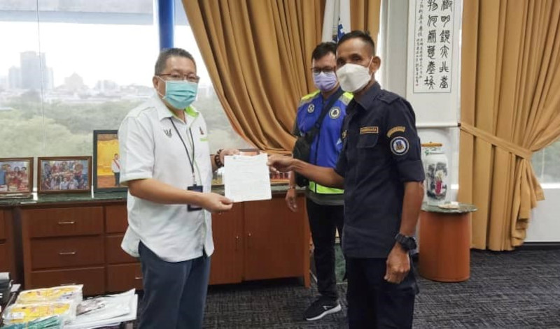 An enforcement officer from Kuching South City Council issuing a compound to Datuk Wee Hong Seng at his office, May 18, 2021. — Picture from Datuk Wee Hong Seng's Facebook