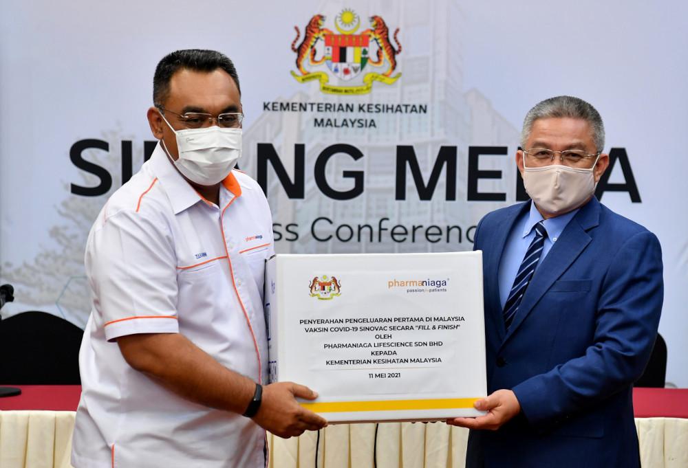 Health Minister Datuk Seri Dr Adham Baba receiving the Sinovac vaccines from Pharmaniaga Bhd managing director Datuk Zulkarnain Md Eusope in Putrajaya, May 11, 2021. — Bernama pic