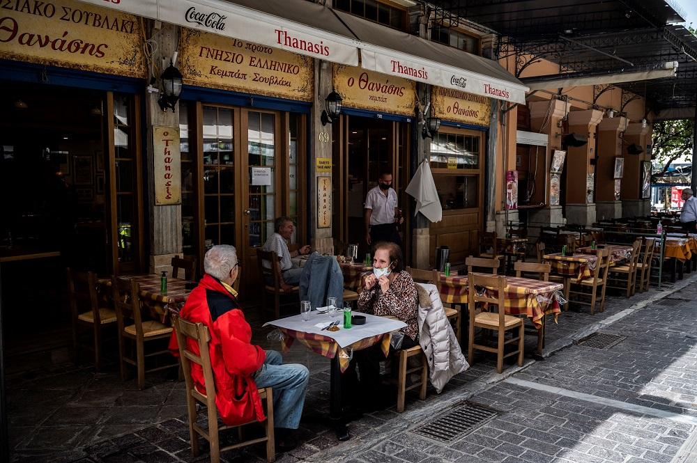 People sit at a restaurant's terrace on Monastiraki square in Athens. ― AFP pic via ETX Studio