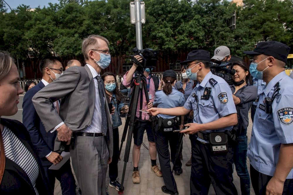 A Chinese police officer returns an ID card to Australian Ambassador to China Graham Fletcher (centre left) as he arrives at the Beijing Second Intermediate People's Court before the trial of Australian academic Yang Jun, also known as Yang Hengjun, on espionage charges in Beijing on May 27, 2021. — AFP pic