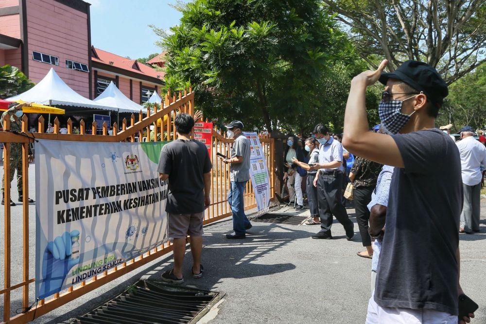 People wait to receive the Covid-19 vaccine outside the Bandar Sri Menjalara community hall in Kuala Lumpur May 25, 2021. ― Picture by Ahmad Zamzahuri