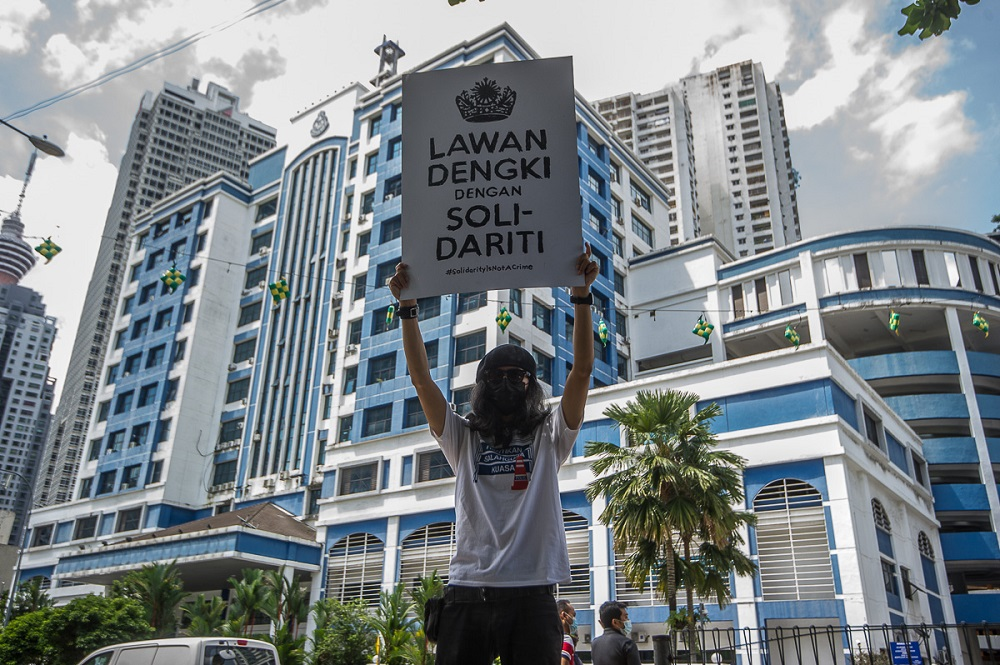 Fahmi Reza holds a placard outside the Dang Wangi district police headquarters in a show of solidarity with Lembah Pantai MP Ahmad Fahmi Mohamed Fadzil. ― Picture by Shafwan Zaidon
