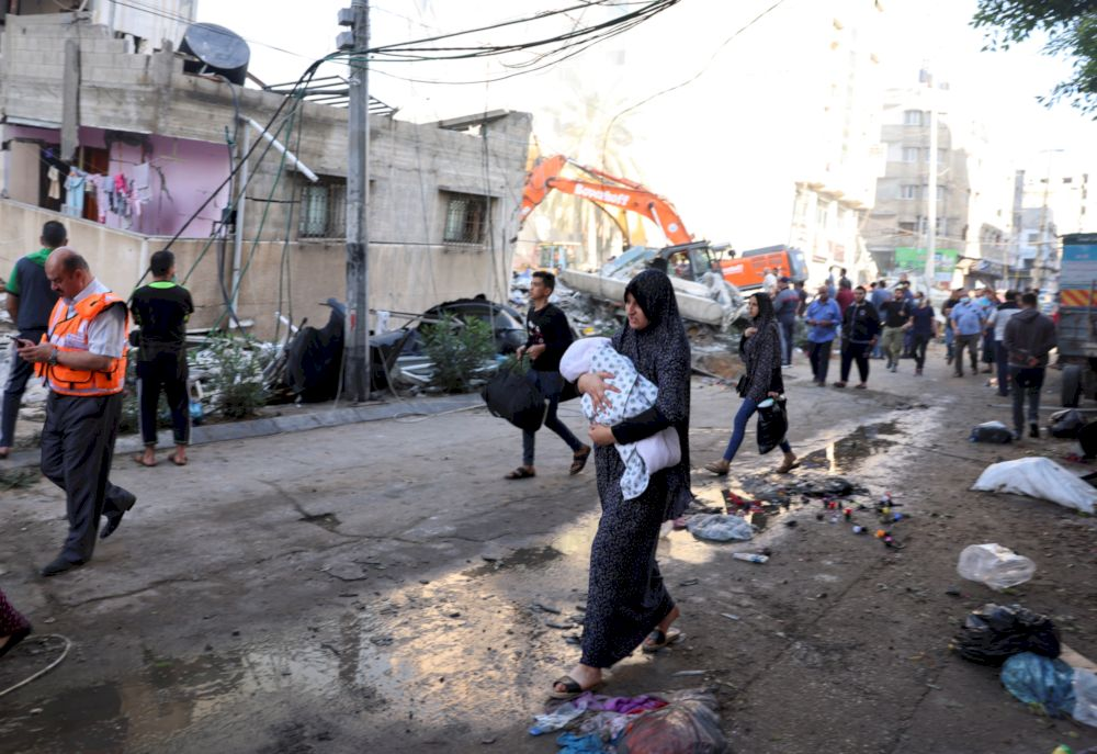 People walk past debris in a street at the site of Israeli air strikes, in Gaza City May 16, 2021. — Reuters pic