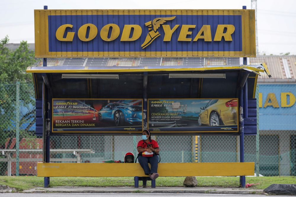 A woman sits at a bus stop outside Goodyear factory in Shah Alam May 6, 2021. — Reuters pic