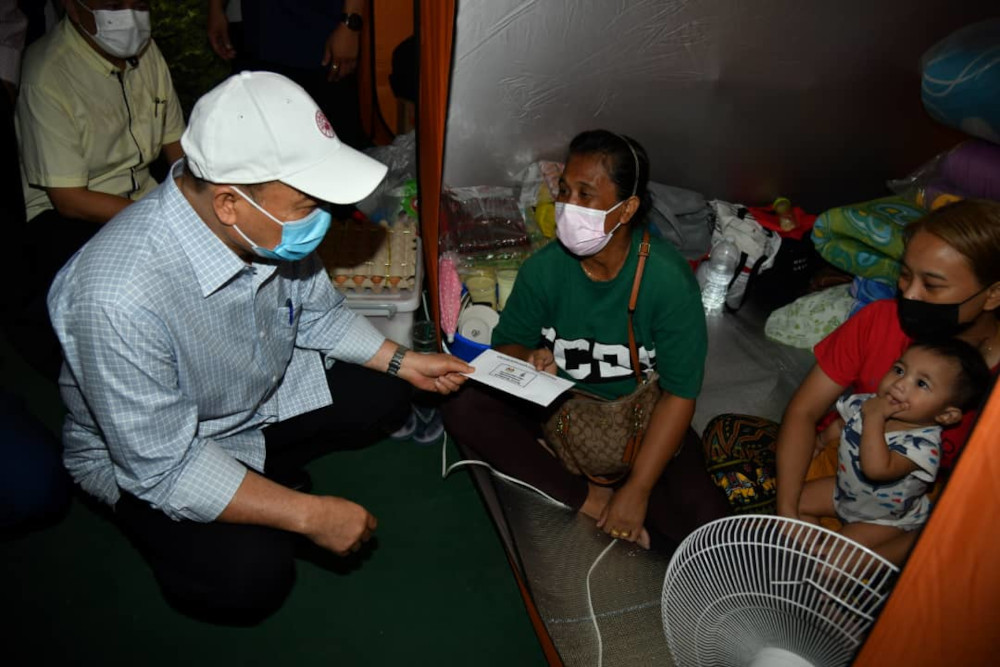 Sabah Chief Minister Datuk Hajiji Noor meeting some of the victims of the fire in Kampung Meruntum last Saturday which saw 35 wooden stilt homes razed. — Picture by Julia Chan