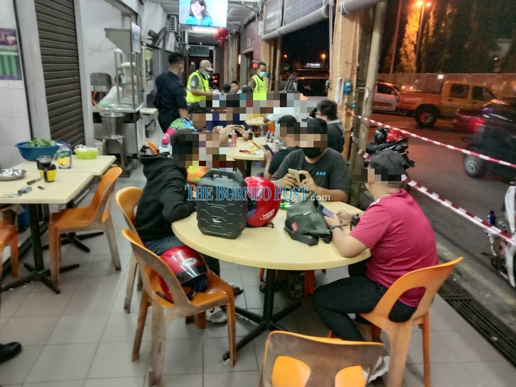 File photo shows police personnel checking on a coffee shop in Kuching for SOP compliance. ― Borneo Post pic