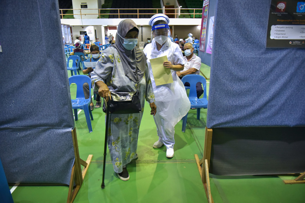 A senior citizen is helped by a nurse at the Labuan Corporation multipurpose hall vaccination centre, May 4, 2021. — Bernama pic