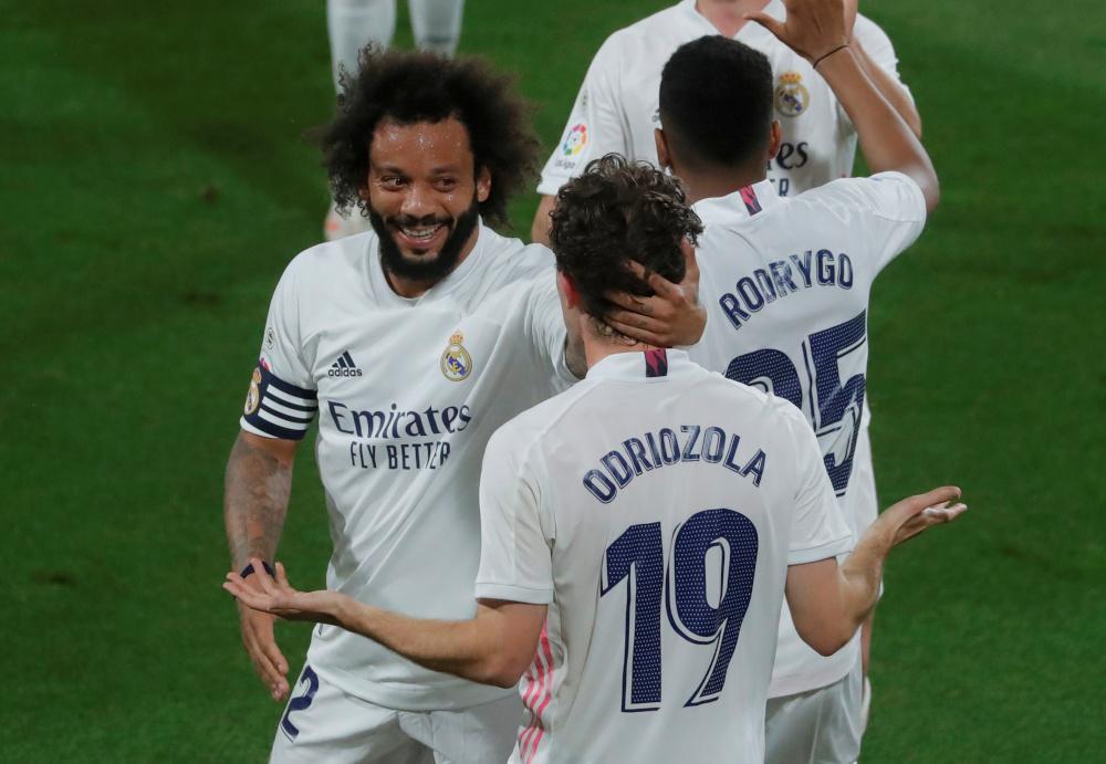 Real Madrid's Alvaro Odriozola celebrates scoring their second goal with Marcelo in a match against Cadiz at the Estadio Ramon de Carranza, Cadiz, Spain, April 21, 2021. — Reuters pic