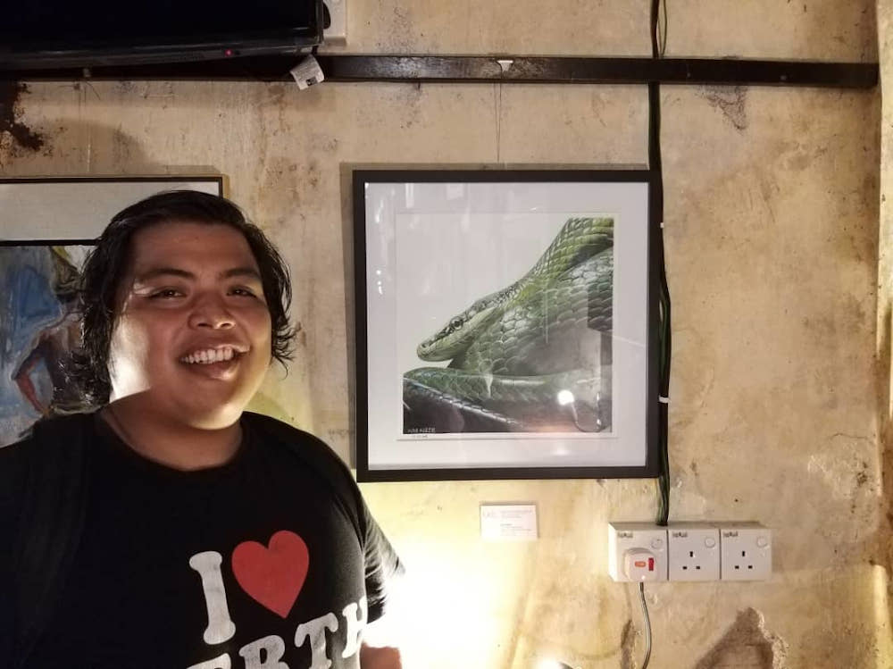 The late artist Nasir with his realistic colour pencil work of a snake titled 'Ulaq Ijau' during the Open Studios Penang 2019 exhibition. — Picture courtesy of Nizom Nadzir