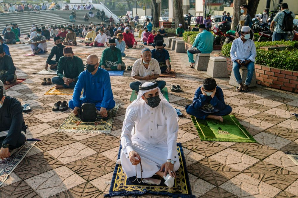 Muslims perform Eid Al-Fitr prayers outside the National Mosque in Kuala Lumpur May 13, 2021. — Picture by Firdaus Latif