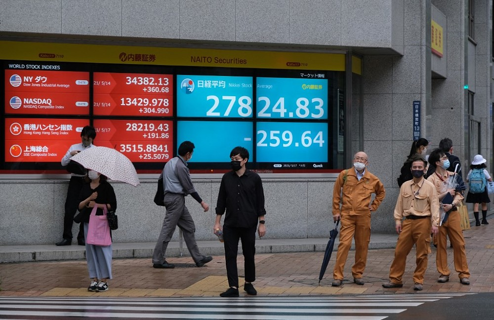 File photo of people standing in front of an electronic quotation board displaying the closing numbers of share price at the Tokyo Stock Exchange in Tokyo, May 17, 2021. — AFP pic