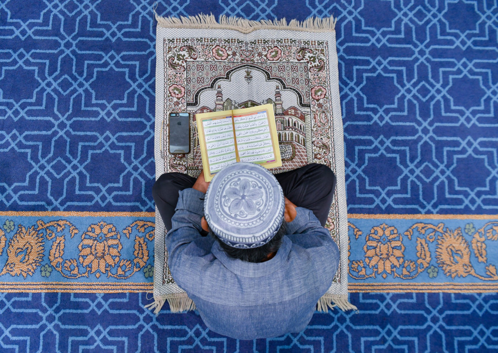 A man recites the Surah Yassin after performing hajat prayer for Palestinians at the Sulan Azlan Shah mosque in Ipoh, May 17, 2021. — Bernama pic
