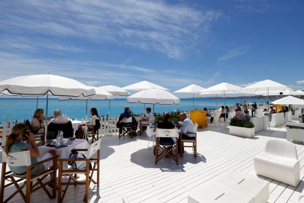 Customers enjoy a lunch on the terrace of a beach restaurant in Nice as cafes, bars and restaurants reopen after closing down for months amid the Covid-19 outbreak in France, May 19, 2021. — Reuters pic