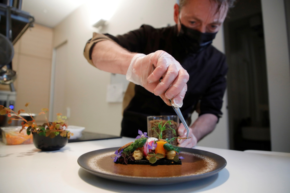 French chef Laurent Veyet prepares a dish made with mealworms in his restaurant Inoveat serving insect-based food in Paris May 12, 2021. — Reuters pic