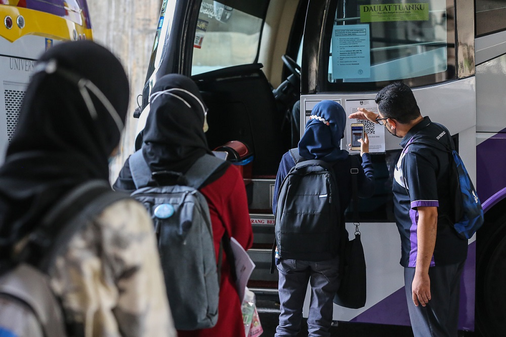 Students scan QR code via the MySejahtera app before boarding the bus at UiTM Shah Alam May 7, 2021. ― Picture by Yusof Mat Isa