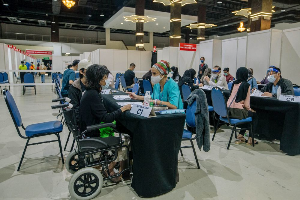 Members of the public register their personal details before receiving the AstraZeneca Covid-19 jab at the World Trade Centre Kuala Lumpur May 16, 2021. — Picture by Firdaus Latif