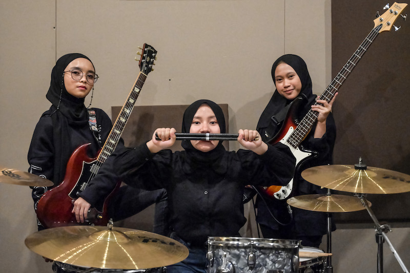 Members of the Indonesian heavy metal band Voice of Baceprot (VOB), (from left) guitarist and vocalist Firda Marsya Kurnia, drummer Euis Siti Aisah and bassist Widi Rahmawati pose for photos after a practice session in Jakarta. — AFP pic