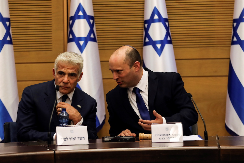 Israeli Prime Minister Naftali Bennett (right) and Foreign Minister Yair Lapid attend its first Cabinet meetiing in the Knesset, Israel's parliament, in Jerusalem June 13, 2021. — Reuters pic
