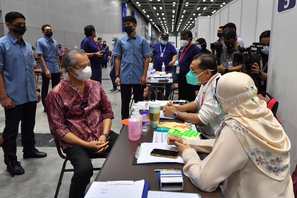 慕尤丁(坐者左)周日到吉隆坡会展中心疫苗接种中心巡视。-马新社-