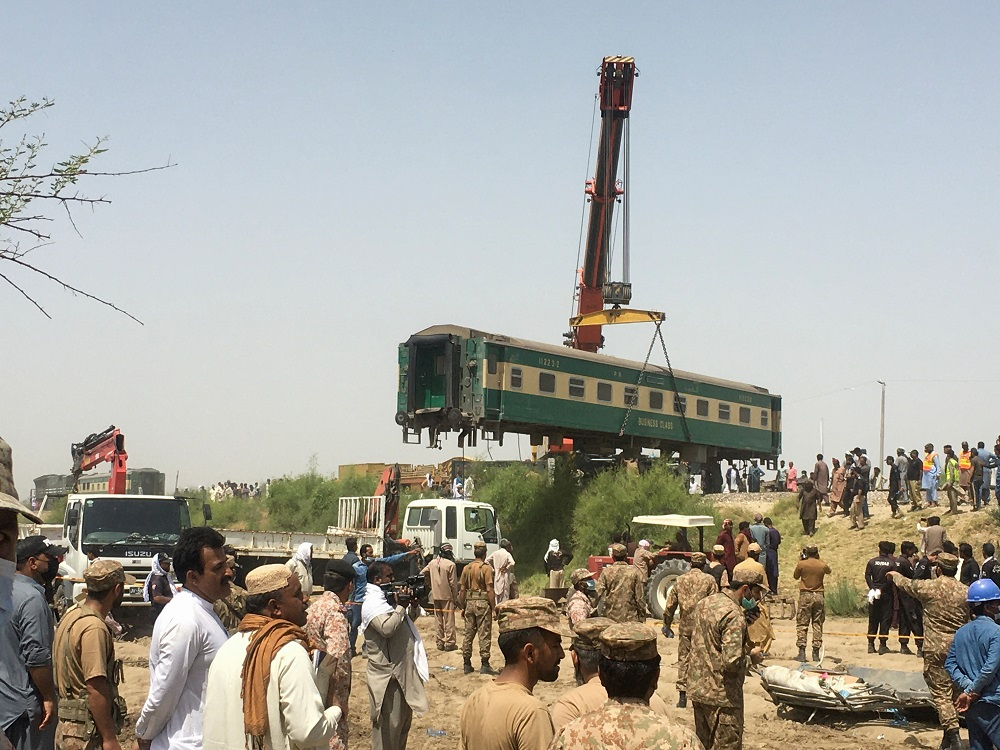 Paramilitary soldiers and residents gather as the railway workers remove a car from the site following a collision between two trains in Ghotki, Pakistan June 7, 2021. — Reuters pic