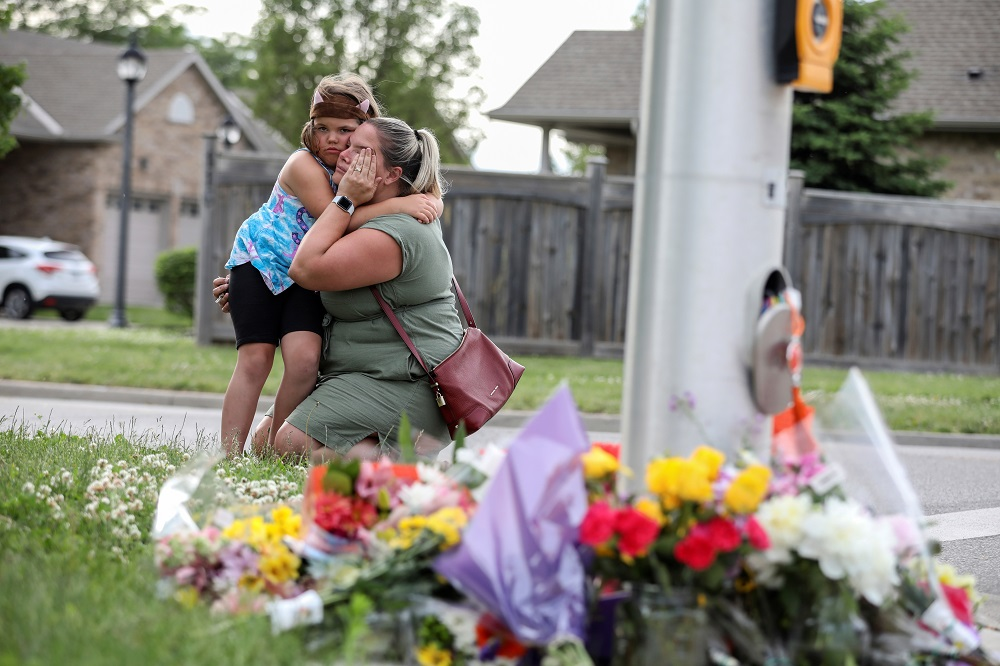 A woman and her daughter react near flowers laid at the fatal crime scene in what police say was a deliberately targeted anti-Islamic hate crime, in London, Ontario June 7, 2021. — Reuters pic