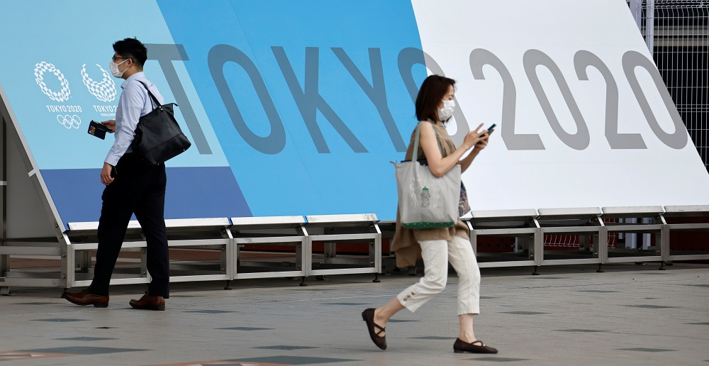 People walk past a sign for the 2020 Tokyo Olympic Games that have been postponed to 2021 due to the coronavirus disease pandemic, at the IBC/MPC media centre at Tokyo Big Sight exhibition centre in Tokyo June 30, 2021. — Reuters pic