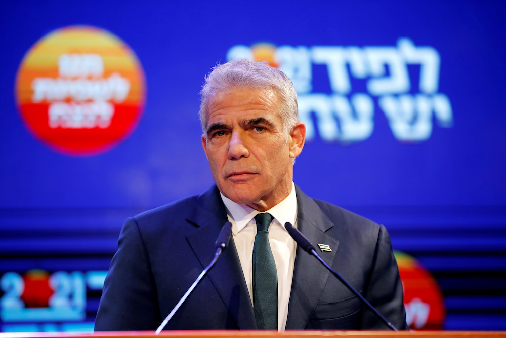 Yesh Atid party leader Yair Lapid delivers a speech following the announcement of exit polls in Israel's general election at his party headquarters in Tel Aviv, Israel March 24, 2021. — Reuters pic