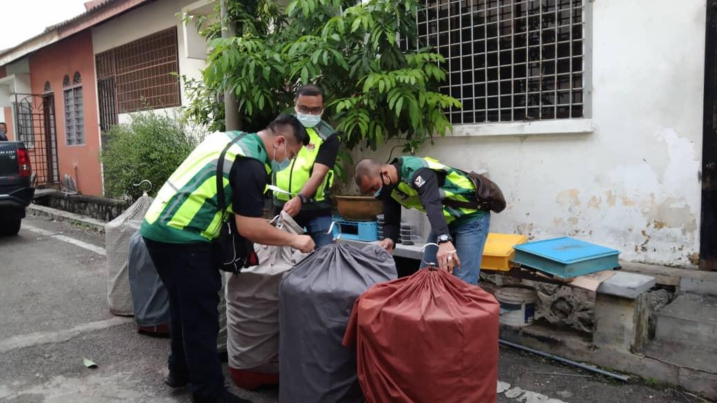 Johor Wildlife and National Parks Department officers inspect the bird cages after a raid at a pet shop in Taman Kota Masai, Pasir Gudang June 4, 2021. — Picture courtesy of Johor Wildlife and National Parks Department